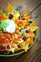 Fully loaded nachos in a green plate on a wooden table