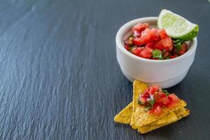 Salsa sauce and nachos in white bowl, dark stone background