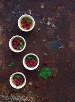 Creme brulees with raspberries and mint in white bowls over
