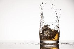 Ice splash into whiskey or brandy