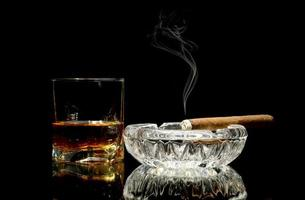 whisky y un cigarro en mesa brillante