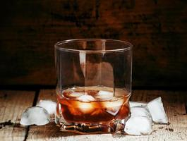 Cold whiskey with ice in a dark cellar