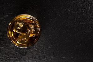 Glass of whiskey with ice on black stone