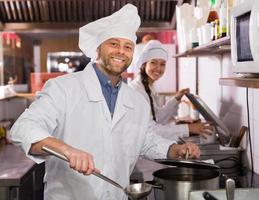 chef y su ayudante en la cocina del bistro foto