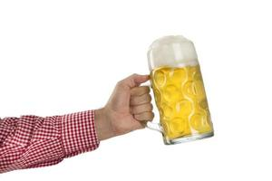 Man in traditional Bavarian shirt holds mug of beer photo