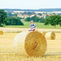 Little kid boy sitting on hay bale in summer