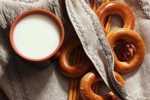 comida leche en un vaso de panecillos de paja y pretzels foto