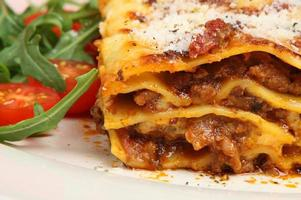 Close-up photo of baked lasagna al forno with side salad