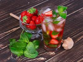 Strawberry mojito cocktail over wooden background