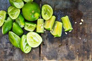 Fresh limes on wooden table, top view