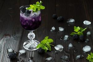Blackberry cocktail in wine glass with mint and ice photo