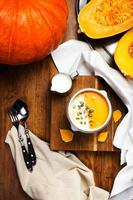 Pumpkin Soup with whipped cream and  seeds in white bowl