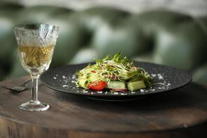 Ensalada fresca de primavera con rúcula, tomate, pepino, cebolla, pimiento foto