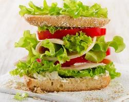 Sandwich with turkey and fresh vegetables on a wooden background