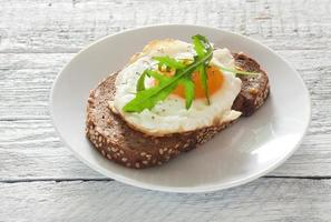 Sandwich with fried egg and arugula