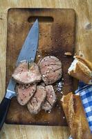 Roast beef on cutting board with salt and pepper