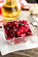 Beetroot salad in clear bowl on grey wooden background