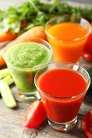 Fresh tomate, carrot and cucumber juice on grey wooden background