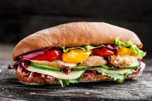 Sandwich with chicken, cheese and vegetables photo