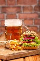Grilled hamburger with fries and beer on brick wall background
