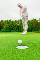 Vertical picture man playing golf on a green field photo