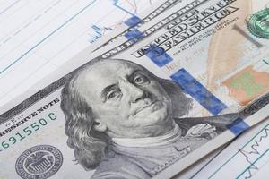 Hundred dollars banknote over stock market graph photo