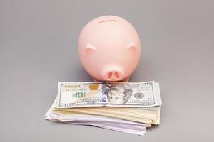 piggy bank with banknotes on gray background