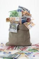 saco de arpillera rebosante de moneda extranjera foto