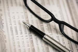 closeup glasses on financial newspaper with pen photo