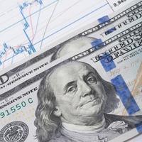 nota de cem dólares americanos sobre o gráfico do mercado de ações