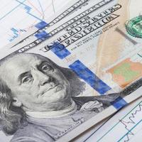 Hundred dollars banknote over stock market candle graph photo