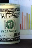 tabla de ventas y billetes de cien dólares en moneda estadounidense foto