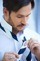 Businessman dressing tying his tie photo