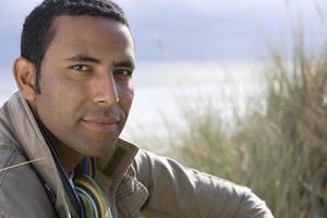 Young man on sand dune, portrait, close-up photo