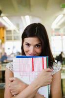 Portrait of happy young businesswoman with books in office photo