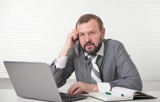 volwassen zakenman die op zijn laptop werkt