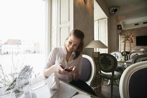 lachende jonge zakenvrouw tekstberichten op mobiele telefoon