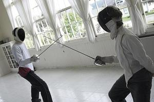 Two people fencing in a white room