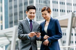 duas pessoas de negócios olhando em um telefone celular