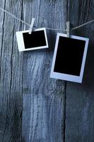 Blank photographs hanging on old wooden wall