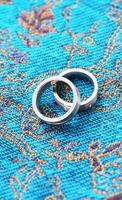 Wedding rings on blue fabric photo