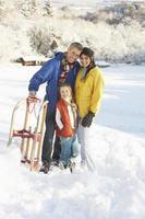 joven familia de pie en paisaje nevado con trineo