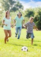 couple and teenager boy playing with soccer ball photo