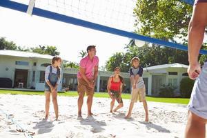 Familia jugando voleibol en el jardín en casa foto