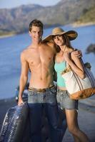Teenage couple near lake, boy holding inflatable, girl wearing h