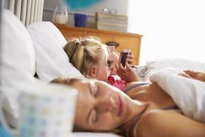 hija juega con el teléfono móvil en la cama mientras los padres duermen foto