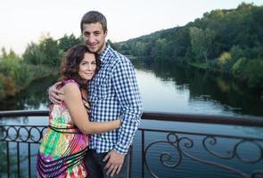 Loving couple stands on bridge.