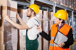 Manager with worker in warehouse photo