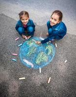 meninas sorridentes, desenhando a terra com giz na rua