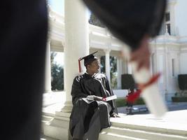 estudiante universitario en toga de graduación y junta de mortero foto